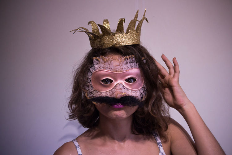 Portrait of woman wearing crown and mask with mustache