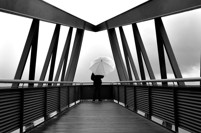 Standing at the reeling Rainy Days The Week On EyeEm Architecture Black And White Friday Built Structure Day Full Length Leisure Activity Lifestyles Lines And Shapes Monochrome Monochrome Photography Nature One Person Outdoors Railing Real People Rear View Sky Symmetrical Symmetry Water Women