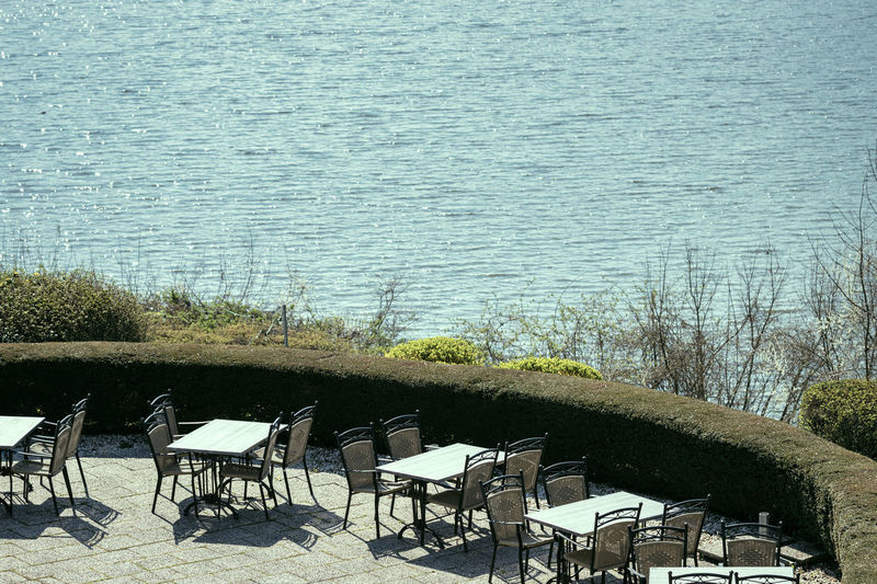 High angle view of empty chairs and table by lake