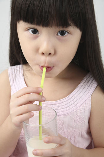 chinese girl enjoy drinking milk Bangs Black Hair Casual Clothing Childhood Close-up Drink Drinking Drinking Glass Drinking Straw Food And Drink Food Stories Freshness Front View Girls Headshot Healthy Lifestyle Holding Indoors  Innocence Lifestyles Looking At Camera One Person Portrait Real People Refreshment White Background
