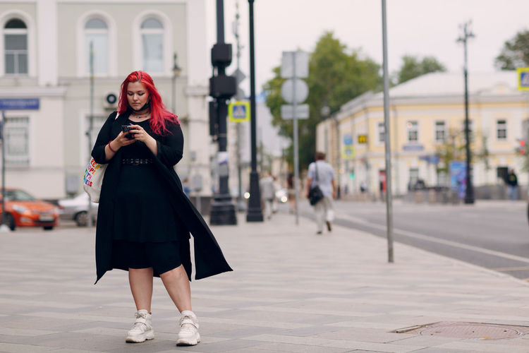 Full length of woman standing on mobile phone in city