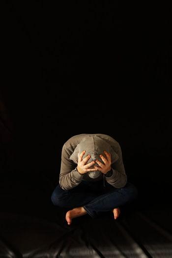 Stressed man sitting against black background