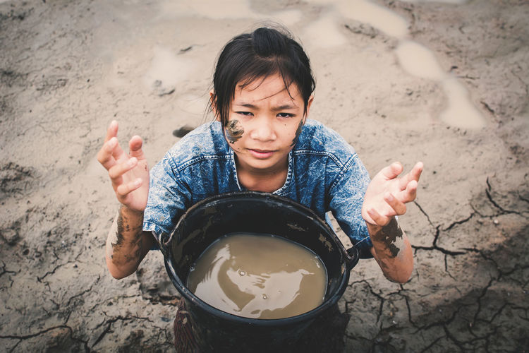 Portrait Of Girl Holding Muddy Water In Container On Ground