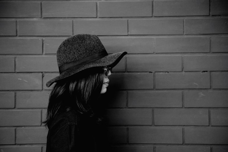 Side view of woman wearing hat against wall