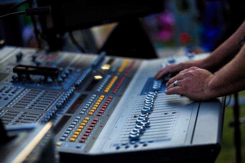 Cropped hands of man playing sound mixer