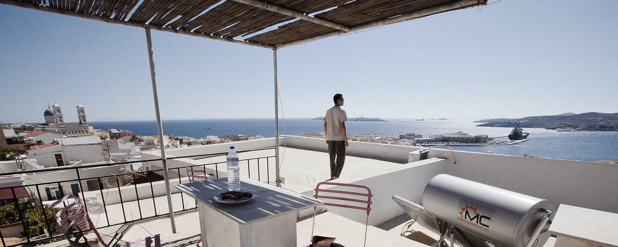 A tourist enjoying scenic rooftop ocean view Ermoupoli Rooftop Travel Architecture Beauty In Nature Boat Deck Built Structure Clear Sky Day Greece Horizon Over Water Leisure Activity Lifestyles Men Nature Nautical Vessel One Person Outdoors People Real People Roof Scenics Sea Sky Standing Syros Transportation Water Women Young Adult