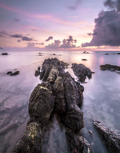 Sunrise with stone at Kemasik Beach taken with Slow Shutter. Soft Focus Motion Blur due to Slow Shutter Speed. Copy Space Area