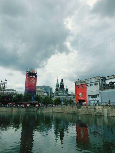 Buildings by lake against sky in city