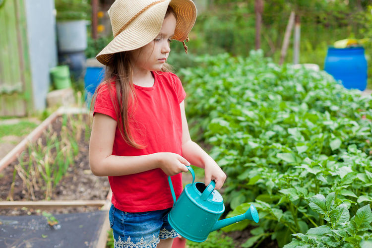 Girl holding watering can while standig by plants
