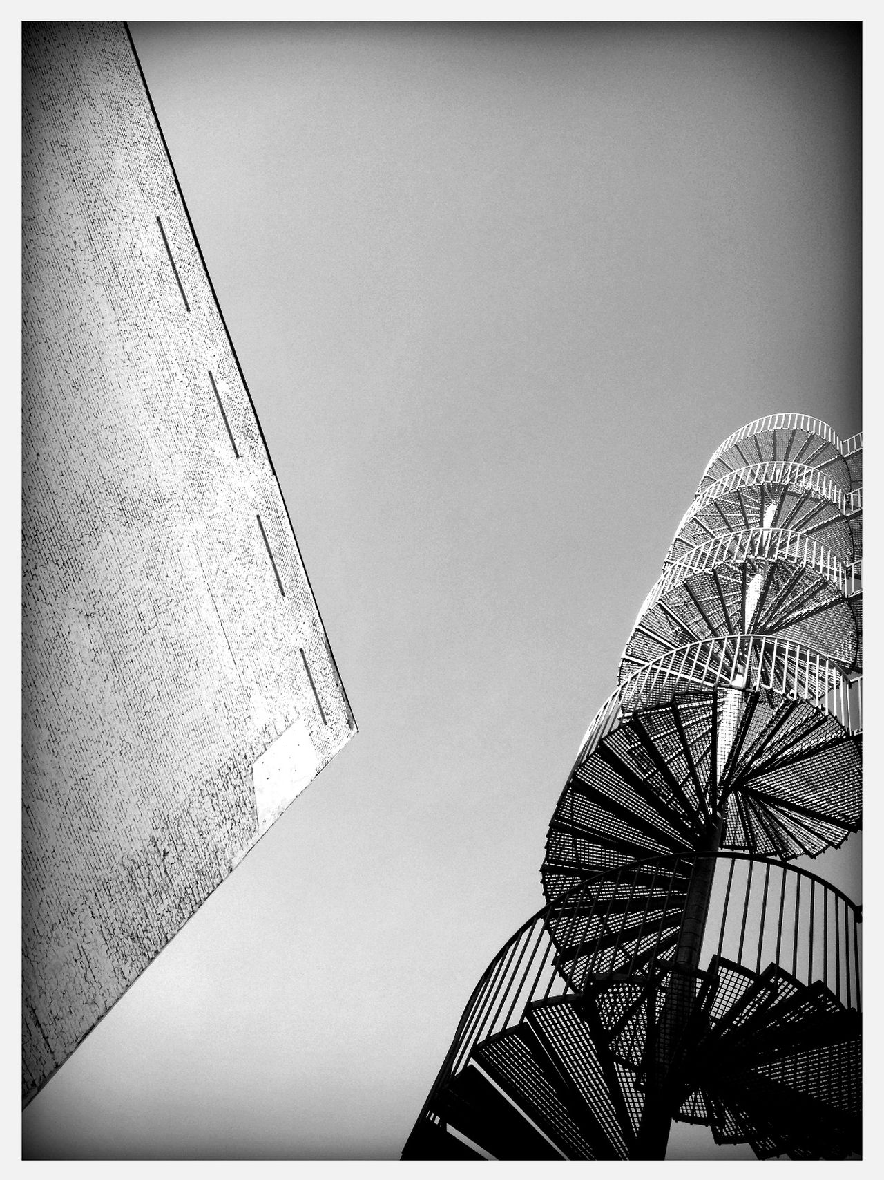 Low angle view of spiral staircase by building against clear sky