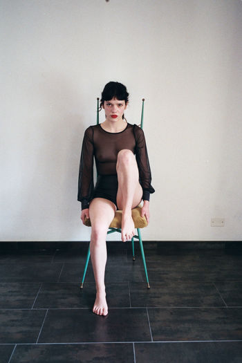 Portrait of woman sitting on tiled floor against wall