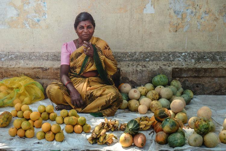 Portrait of smiling market vendor wearing sari selling fruits at market stall