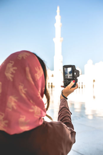 Rear View Of Woman Photographing Mosque With Camera