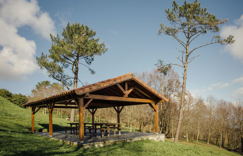 Wooden pavillion with picnic tables over nature background Autumn Calm Cloudy Cloudy Sky Field Gazebo Grass Green Horizontal Nature Picnic Sunlight Empty Landscape Meadow Mountains Nobody Outdoor Pavilion Peaceful Picnic Table Season  Sky Suny Table