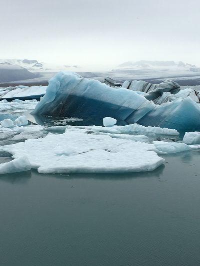 Icebergs on lake against sky
