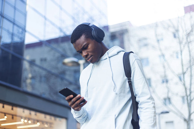 Young man listening to music while using phone outside building