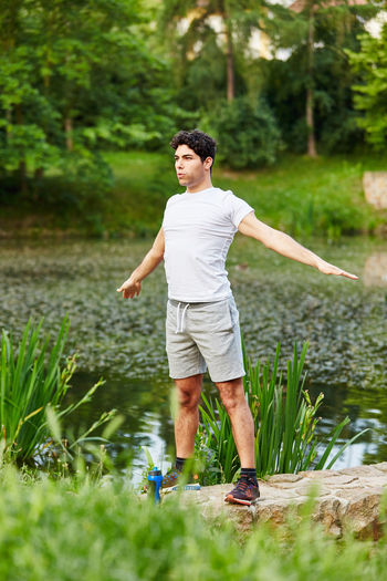 full length of young man standing against plants Active Athlete Boy Casual Clothing Day Exercise Fit Fitness Full Length Grass Green Color Growth Health Healthy Jog Jogger Jogging Leisure Activity Lifestyle Lifestyles Man Men Nature One Person Outdoors Outside Park People Plant Real People Run Runner Shorts Sport Standing Stretch Stretching Summer Teenager Training Tree Vital Warm Up Water Workout Young Young Adult Young Men