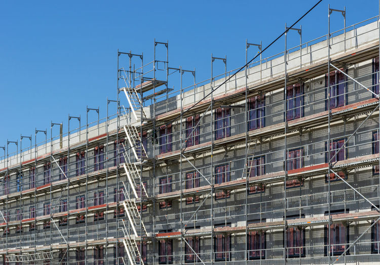 construction site of a building with scaffolding at the facade Architecture Built Structure Building Exterior Low Angle View Clear Sky Construction Industry Scaffolding Construction Site Industry Building Nature Incomplete No People Sunlight Window Modern Sky Outdoors Day Blue City Frame