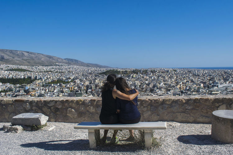 Rear view of two female friends sitting on bench against blue sky