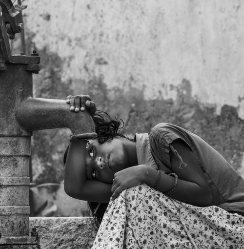 Girl trying to drink water from hand pump against wall