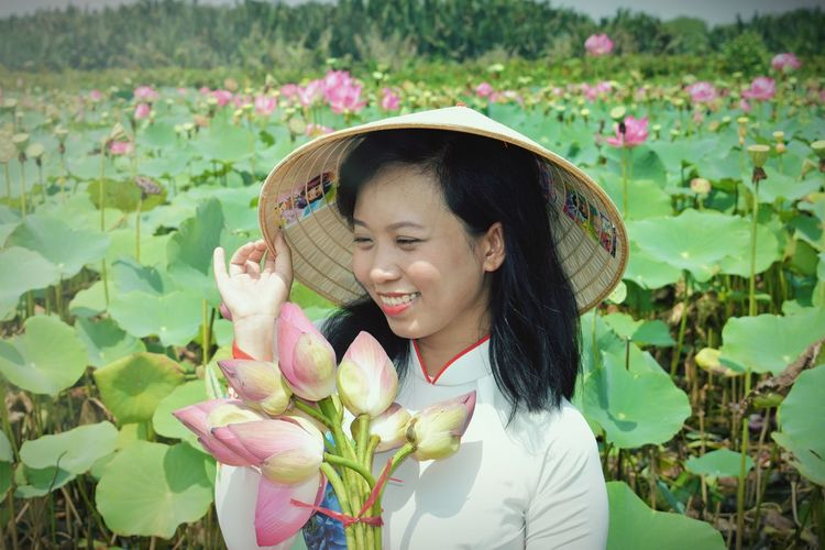 Smiling Woman In Hat Standing Amidst Flowers