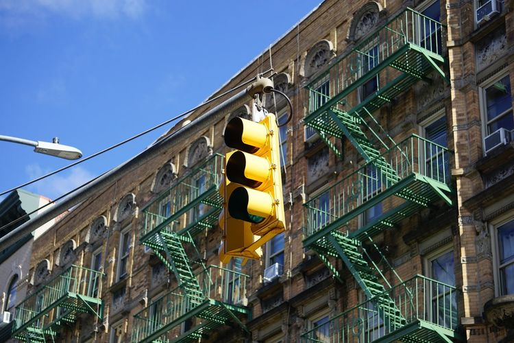 Low Angle View Of Road Signal Against Building In City During Sunny Day