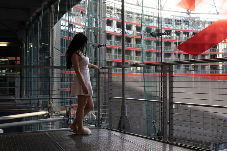 Side View Of Woman Standing By Railing