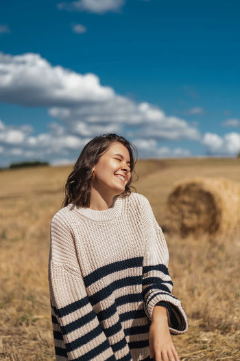 Smiling young woman standing on field against sky