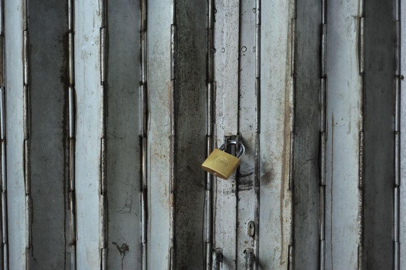 Close-up of padlocks on metal door