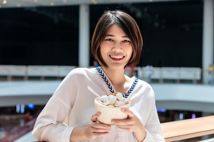 Portrait of a smiling young woman holding ice cream