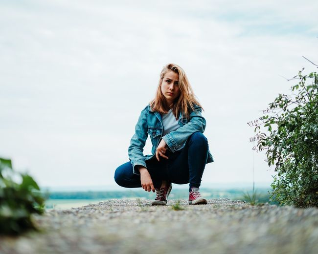 Full length portrait of young woman crouching against sky