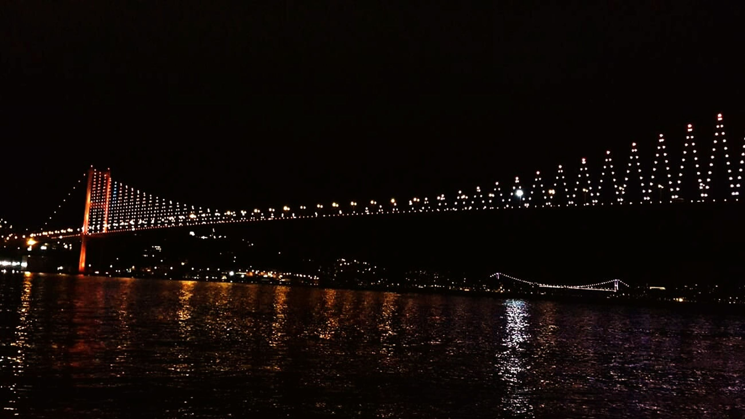 night, illuminated, water, architecture, built structure, waterfront, bridge - man made structure, river, connection, city, reflection, clear sky, copy space, building exterior, bridge, lighting equipment, dark, sea, outdoors, sky