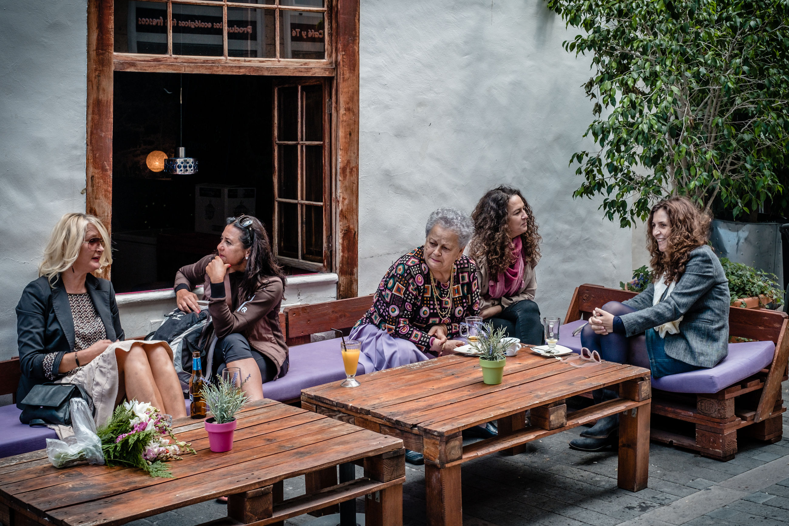 sitting, togetherness, friendship, table, casual clothing, leisure activity, day, real people, food and drink, drinking, lifestyles, enjoyment, young adult, outdoors, talking, young women, relaxation, full length, cafe, women, drink, men, bonding, alcohol, smiling, happy hour, adult, people, adults only