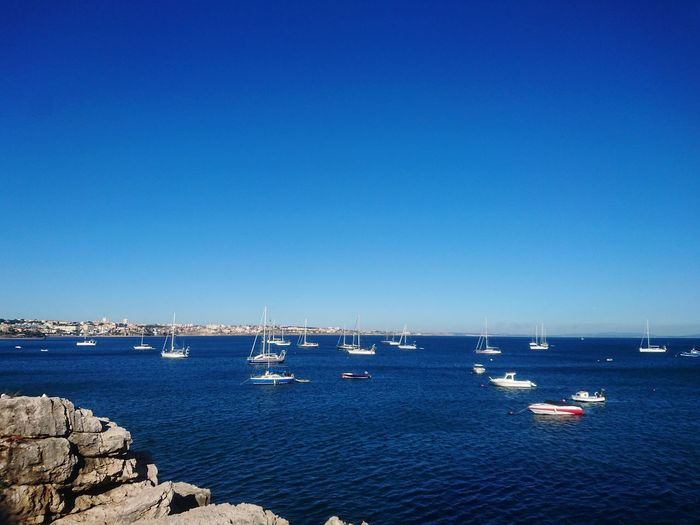 Boats Sailing In Sea Against Clear Blue Sky