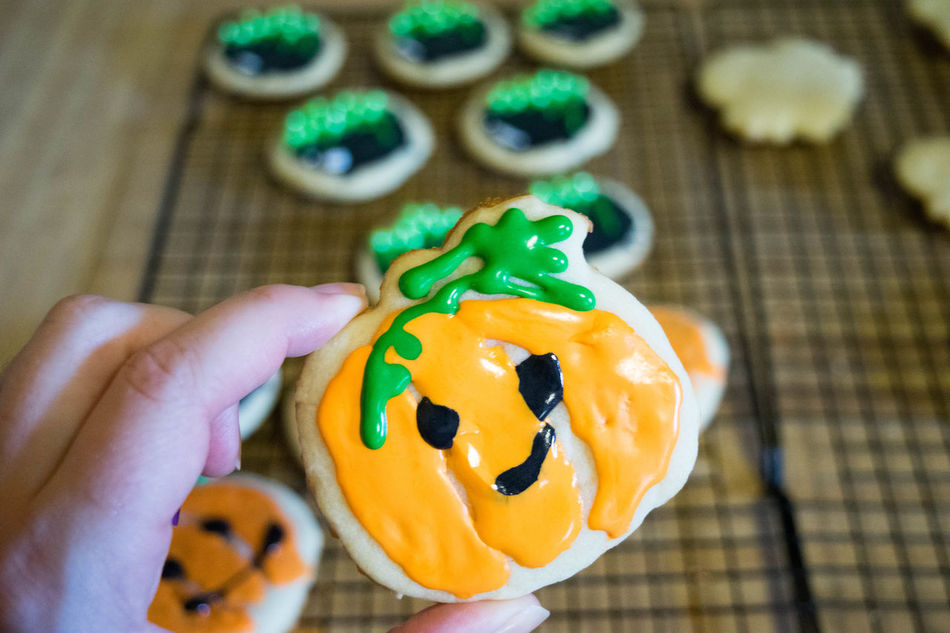 Baked Goods Cookies Halloween Halloween Treats SugarCookies Treats Anthropomorphic Face Close-up Day Festive Focus On Foreground Food Food And Drink Freshness Halloween High Angle View Human Body Part Human Hand Indoors  One Person People Pumpkin Real People Sugar Cookies Sweet Food