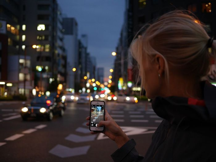 Close-up of woman using smart phone on street at night