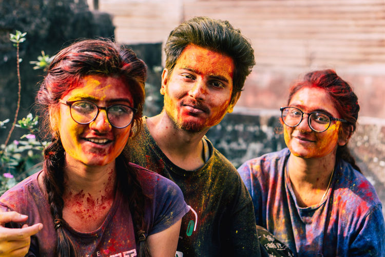 Portrait of smiling friends covered with powder paint outdoors