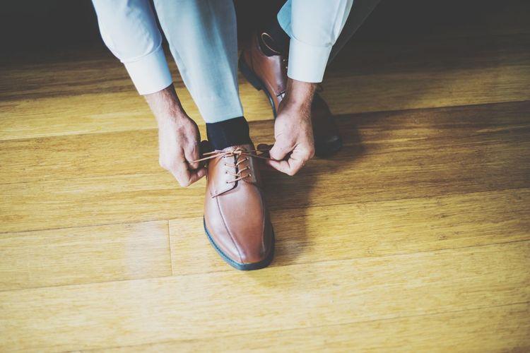 Low section of man tying shoelace on hardwood floor