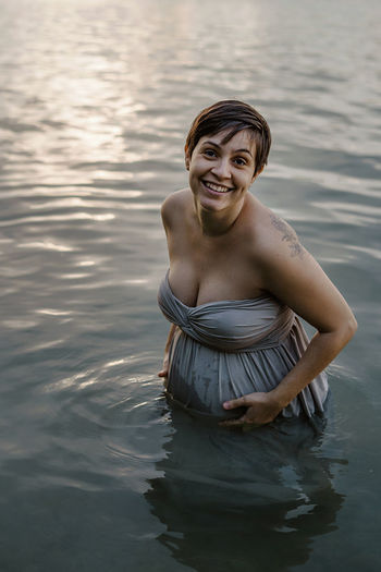 Portrait of a smiling young woman standing in lake