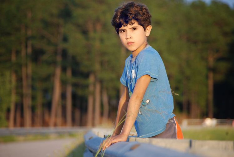 Serious boy leaning on fence on field