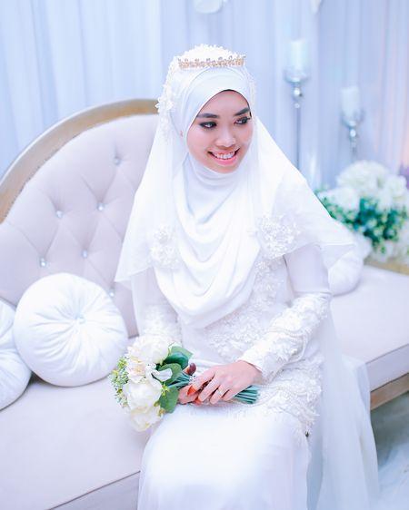 Smiling bride wearing wedding dress sitting on sofa