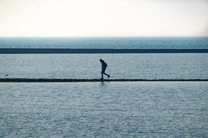 Silhouette man standing in sea against clear sky