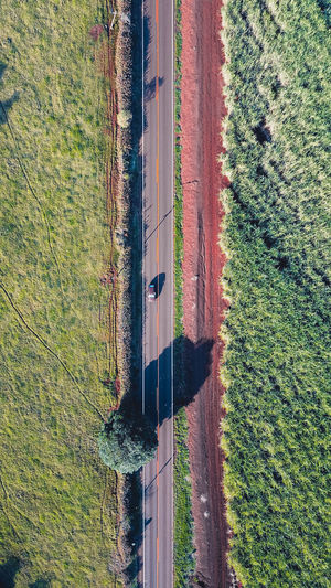 Aerial view of road amidst grassy field