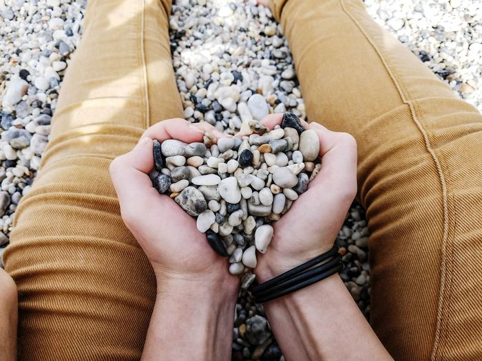 Cropped Image Of Man Holding Pebbles While Sitting At Beach