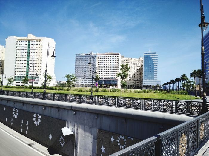 Bridge over canal amidst buildings in city against sky
