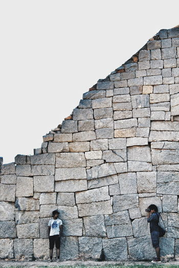 Rear view of woman walking on stone wall