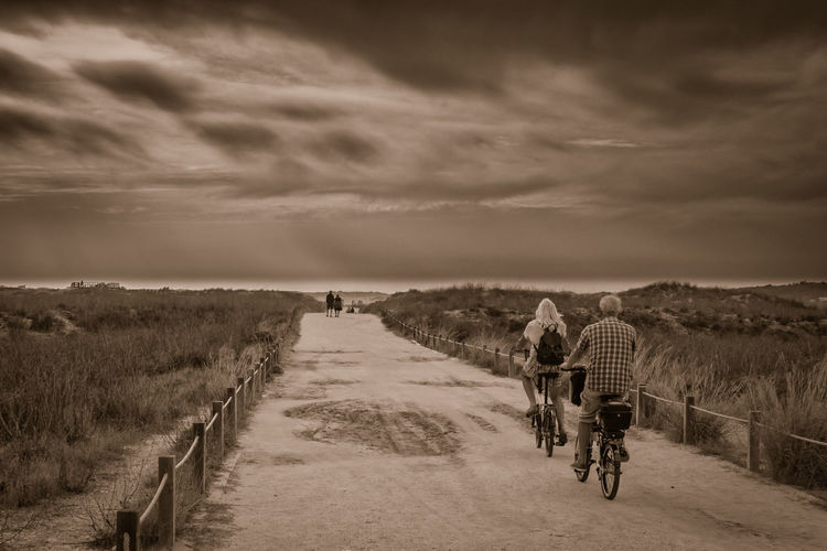 Rear view of men and woman cycling on dirt road against sky