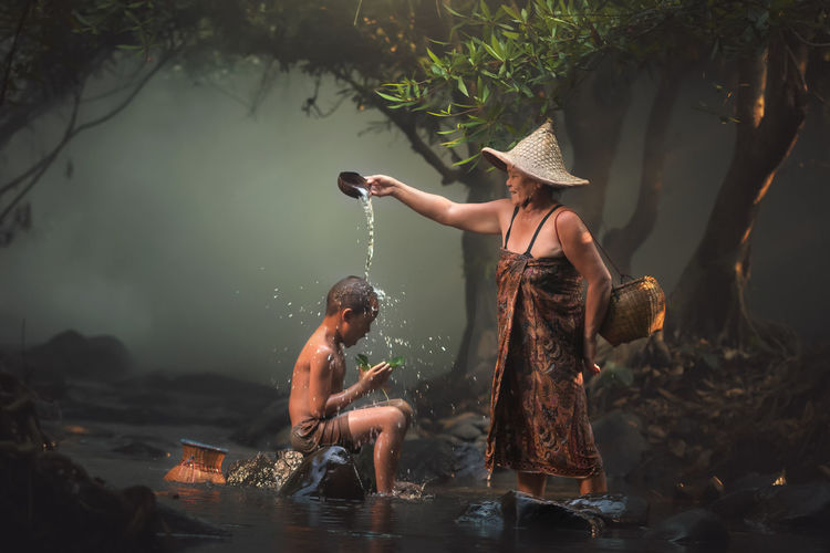 Mothar is bathing her son at the river in Day Friendship Full Length Leisure Activity Lifestyles Men Nature Outdoors People Real People River Shirtless Standing Togetherness Tree Two People Water Women