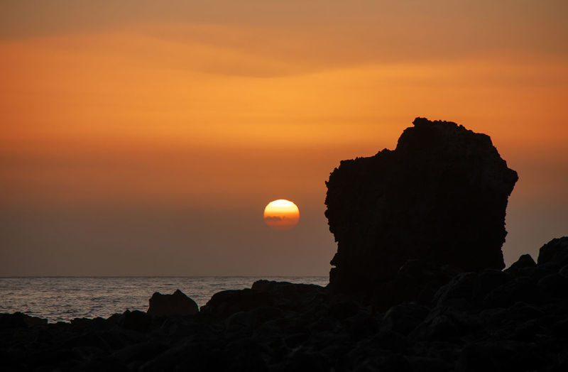 Silhouette rock formation on sea against sky during sunset