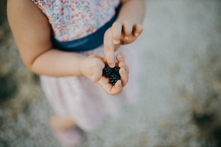 Close-up of girl hand holding berries outdoors
